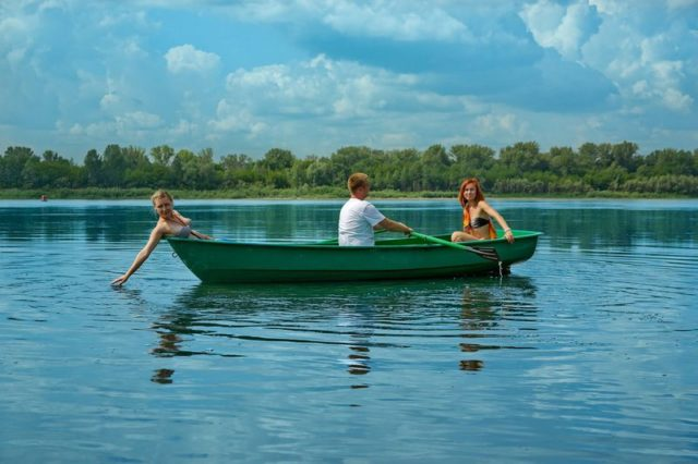 Мужик катает двух женщин на лодке Голавль