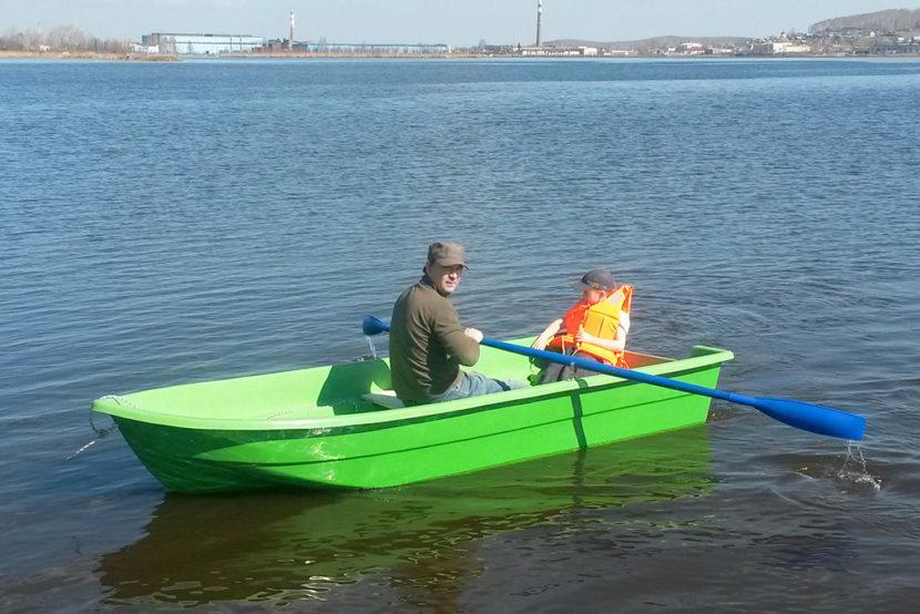 Мужчина катает ребенка на лодке Голавль